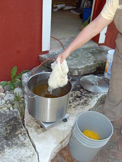 white yarn into yellow dye bath